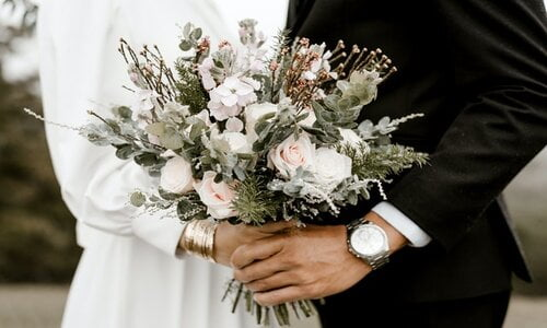 wedding couple posing with bouquet
